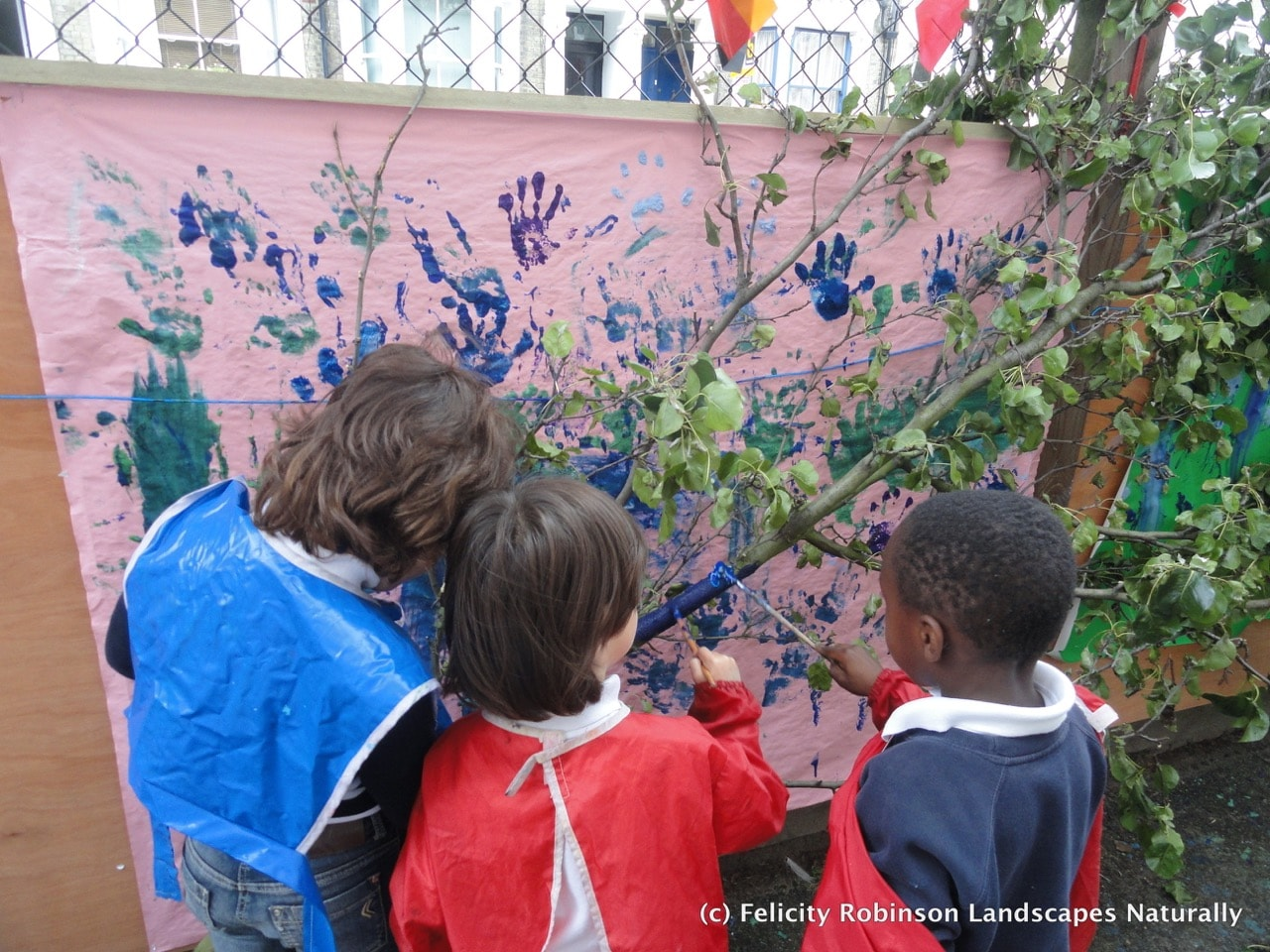 Children painting a tree in the art zone