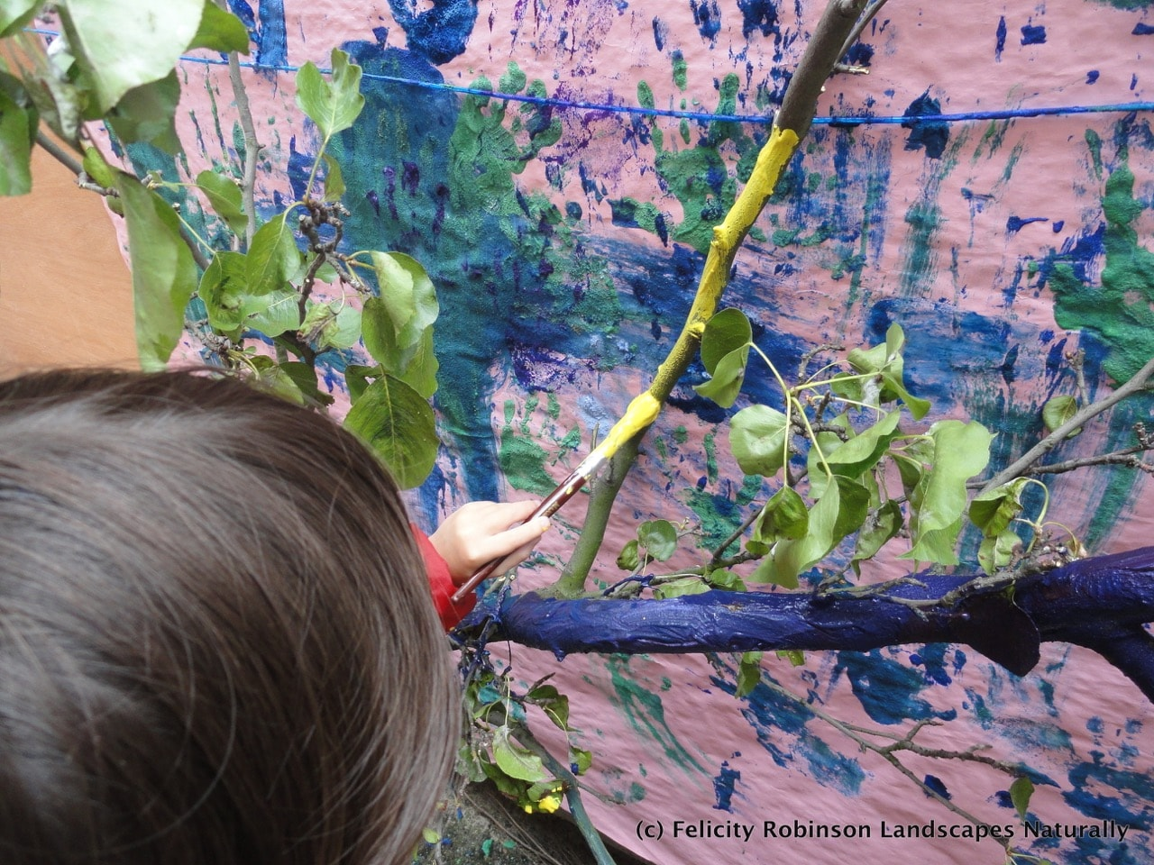 Child painting a tree in the art zone